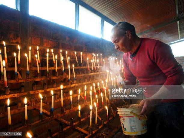 SAPALLANGA HUANCAYO JUNIN PERU A devotee surrounded in vapour lighting candles for the Virgin of Cocharcas in the church of Sapallanga in Huancayo...
