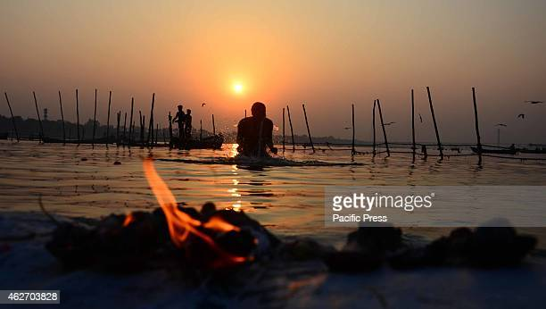 A devotee taking holydip at Sangam during the one month long Magh mela festival
