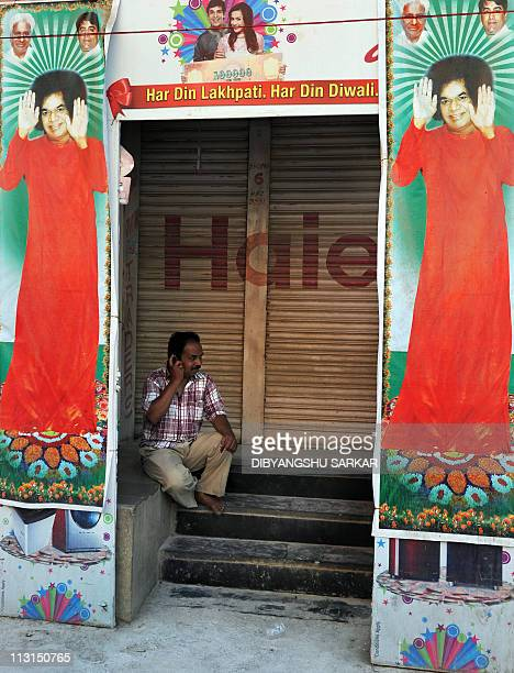 A devotee talks on his mobile phone surrounded by posters of Hindu guru Sathya Sai Baba outside Prashanthi Nilayam at Puttaparthi village some 200...