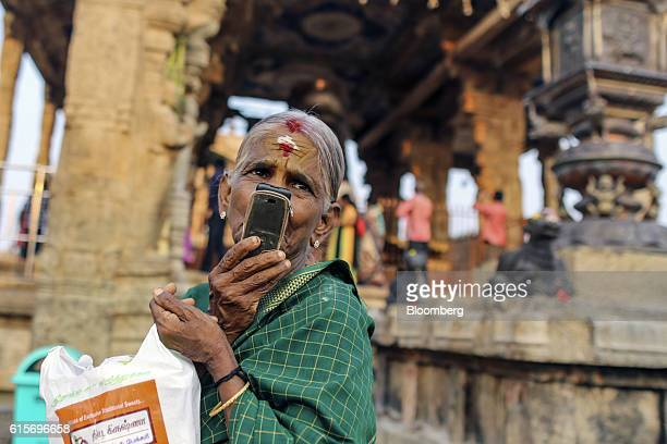 Devotee talks on mobile phone outside the Brihadeshwara Temple in Thanjavur, Tamil Nadu, India, on Sunday, Oct. 16, 2016. India's new central bank...