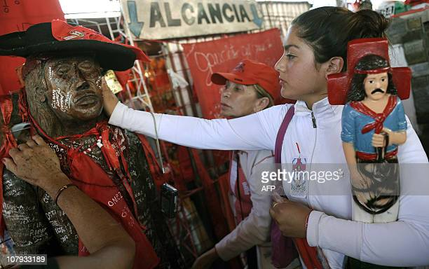 A devotee touches a wooden image of folk saint Gauchito Gil at his sanctuary near Mercedes in the Argentine province of Corrientes on January 8 2011...