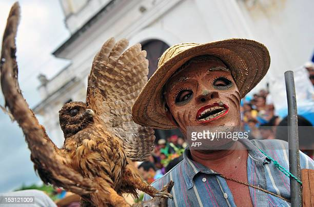 A devotee wearing a traditional mask takes part in a procession during celebrations for San Jeronimo the patron saint of Masaya 30 km from Managua on...