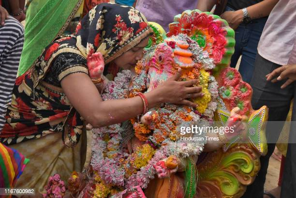 Devotee whispers her wishes and prayers to an idol of Lord Ganesh before its immersion into a temporary pond on the last day of the Ganesh Chaturthi...