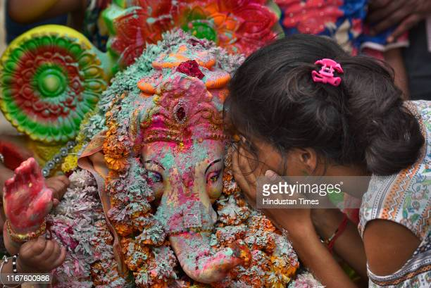 Devotee whispers her wishes and prayers to idol of Lord Ganesha before its immersion into a temporary pond on the last day of the Ganesh Chaturthi...