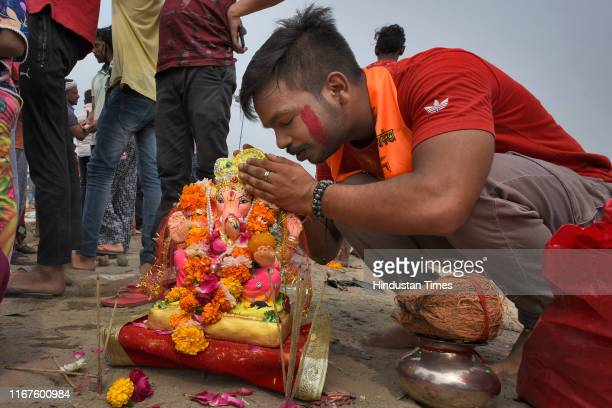 Devotee whispers his wishes and prayers to idol of Lord Ganesh before its immersion into a temporary pond on the last day of the Ganesh Chaturthi...