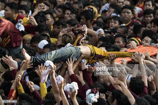 A devotee who collapsed is carried by the crowd during the annual religious Black Nazarene procession in Manila on January 9 2018 A sea of heaving...