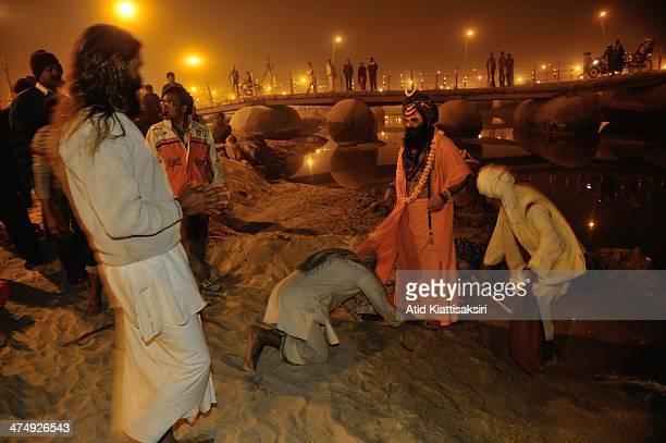 Devotee worships a Sadhu during Maha Kumbh Mela at the Sangam or confluence of Yamuna, Ganges and mythical Saraswati rivers.