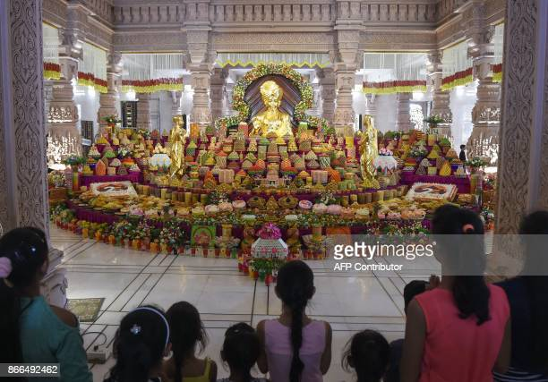 Devotees admire an Annakut or mountain of food on the occasion of Labh Pancham at the end of the Diwali celebrations in front of an idol of the Hindu...