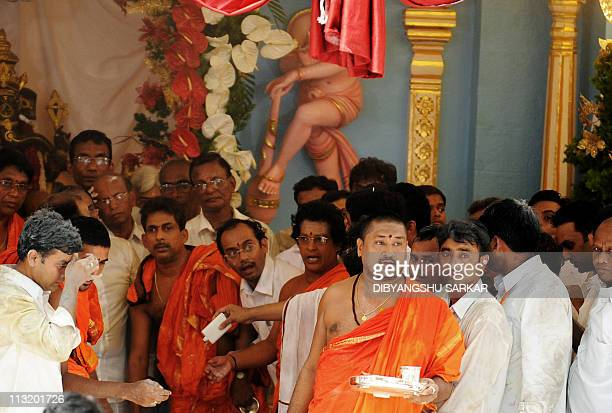 Devotees and volunteers look on as curtains are drawn after the final rituals of the burial of Hindu guru Sathya Sai Baba inside Prashanthi Nilayam...