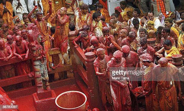 Devotees are soaked in liquid vermillion as it poured over the monolithic statue of Jain sage Gomateswara during the first day of the Mahamastak...