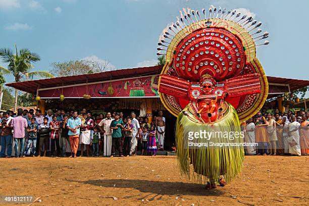 Devotees are watching a Theyyam named, 'Bhagavathi' at a temple in Payyanur in Kerala.Fire is an important component in few types of Theyyam...