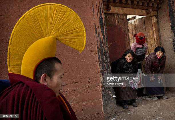 Devotees bow to a passingTibetan Buddhist monk on his way to take part in a special prayer during Monlam or the Great Prayer rituals on March 5 2015...