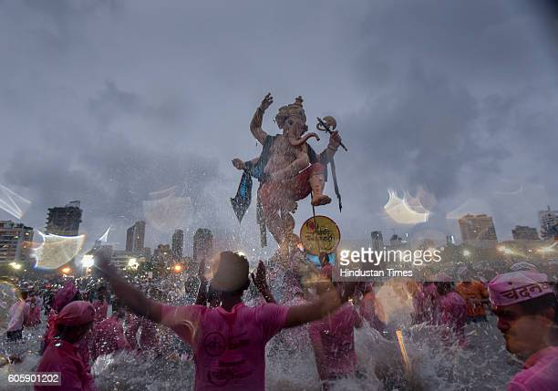 Devotees carry a large statue of the elephantheaded Hindu God Ganesha to immerse it in the Arabian Sea on the final day of the festival of Ganesh...