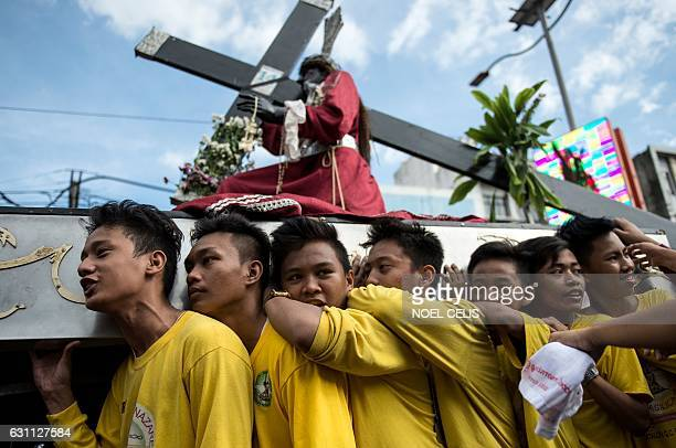 Devotees carry a replica of the Black Nazarene along a road during a procession in Manila on January 7, 2017. Hundreds of thousands of barefoot...