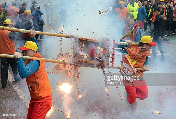 Devotees carry a Taoist god statue as fire crackers are detonated during a lunar festival event at the Yehliu harbor in New Taipei City on February 5...