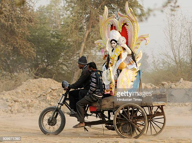 Devotees carry an idol of Goddess Saraswati to immerse during the Vasant Panchami festival or Basant Panchami on February 13 2016 in Noida India...