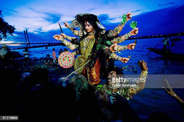 Devotees carry an idol of Hindu goddess Durga before immersing it in the river Ganges on the last day of the Durga Puja festival on September 28 2009...