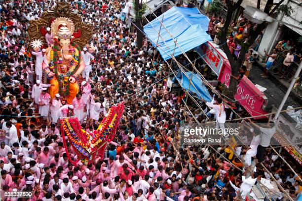 devotees carry ganesh idol for immersion - ganesh chaturthi stock photos and pictures