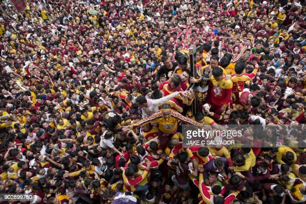 Devotees carry the statue of the Black Nazarene to the carriage during the annual religious procession in Manila on January 9 2018 A sea of heaving...