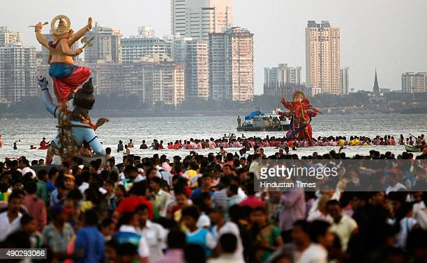 Devotees carrying idols of Hindu Llord Ganesha to immerse in river on the last day of the Ganesh Chaturthi festival at Girgaon Chowpatty on September...