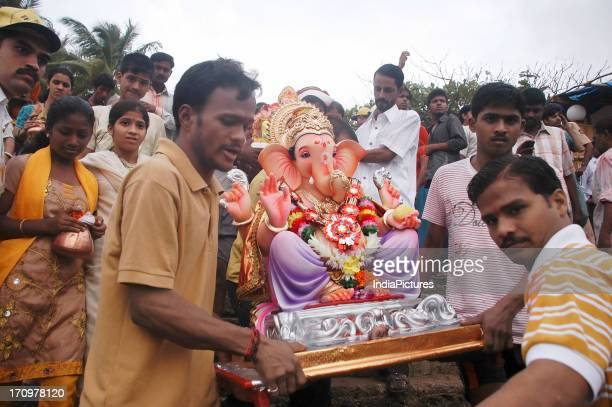Devotees carrying the statue of the Hindu elephant god Ganesh for immersion in the sea on the last day of Ganesh Chaturthi Mumbai Maharasthra India