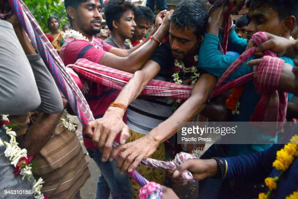 Devotees catch the devotees who perform holy jump from pole during the Charak Puja festivalBengali observes Charak Puja on the last day of Bengali...