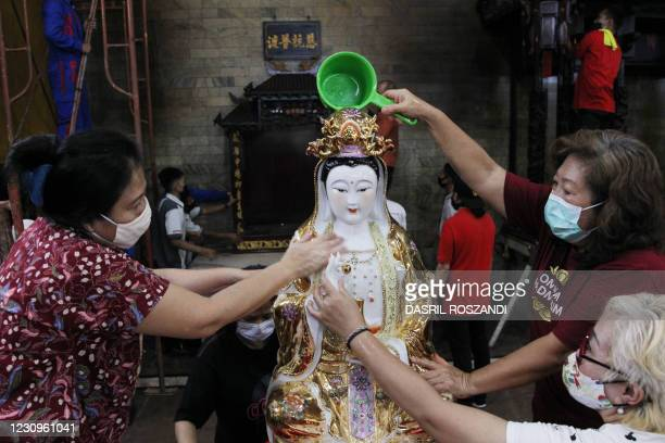 Devotees clean a statue of a deity at a temple in Jakarta on February 4 ahead of the Lunar New Year on February 12.