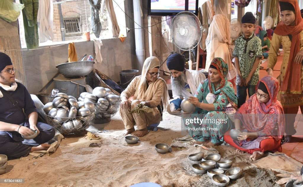Devotees cleaning Sarbloh Utensils after langar at Rangla Sahib on April 25 2017 in Amritsar India Sarbloh is the metal used in the Bata used by Guru.