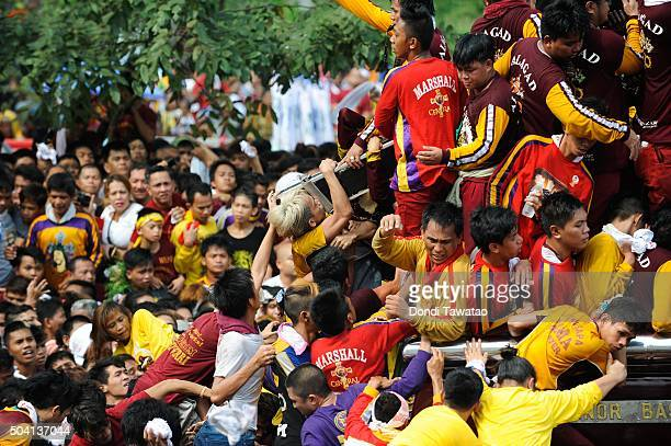 Devotees climb the carriage of the Black Nazarene during the Feast of the Black Nazarene on January 9 2016 in Manila Philippines The Feast of the...