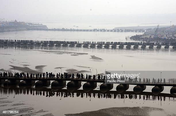 Devotees crossing at the temporary pontoon bridge on river Ganga to arrive Sangam on the eve of 'Mauni Amavasya' the main bathing day during Magh...