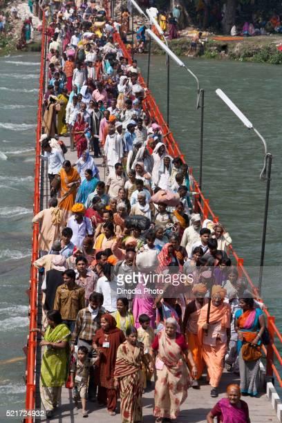 devotees crossing bridge ganga river, haridwar, uttarakhand, india, asia - kumbh mela stock pictures, royalty-free photos & images