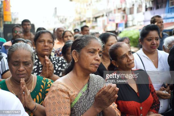 Devotees cry as they pray near St Anthony's Shrine in Colombo on April 28 a week after a series of bomb blasts targeting churches and luxury hotels...