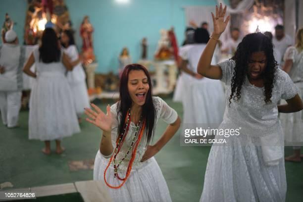 Devotees dance in trance during a ceremony in honour of the Umbanda spirits of Exu and Pombagira in Rio de Janeiro Brazil on October 20 2018 Umbanda...