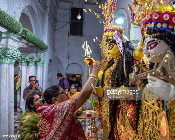 Devotees during Debi Baron rituals to goddess Durga on the day of Dashami by Hindu women at a Traditional Bonedi Bari in Kolkata.