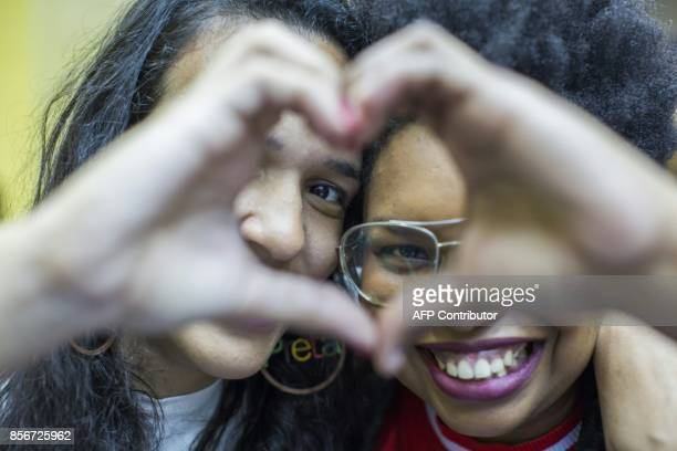 Devotees Elizabeth Cristina 24 and Anna Bomfim 26 make the heart sigh as they participate in the Sunday service at the Contemporary Christian Church...