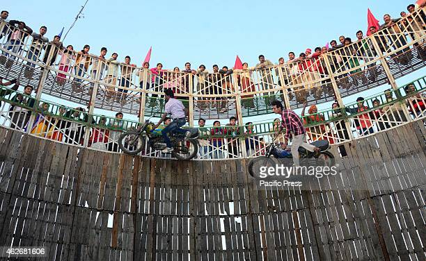 Devotees enjoy watching 'Well of Die' as peformers drive motorcycles on the wall during Magh Mela festival