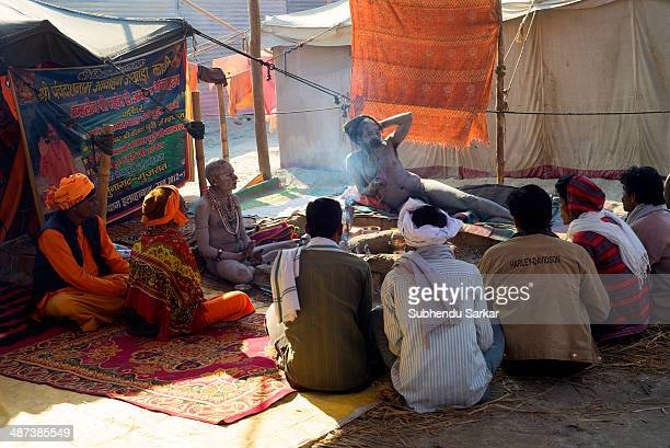 Devotees gather at a sadhu's camp in Maha Kumbh mela. Kumbh Mela is a site of mass pilgrimage in which Hindus gather at a sacred river for a holy...