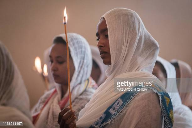 Devotees hold candles during a special service for the families of the victims of the crashed Ethiopia Airlines at Ethiopian Orthodox Church in...