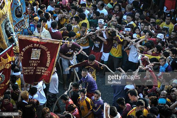 Devotees hold on to the rope that pulls the carriage of the Black Nazarene during its procession in Manila Philippines January 9 2014 The Black...