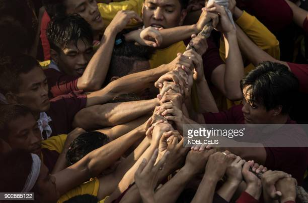 Devotees hold onto a rope connected to the carriage carrying the statue of the Black Nazarene during the annual religious procession in Manila on...