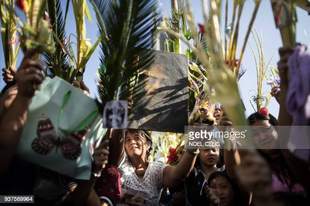 TOPSHOT Devotees hold palm fronds as a layman of the Roman Catholic Church blesses palms during Palm Sunday celebrations at the Our Lady of Lourdes...