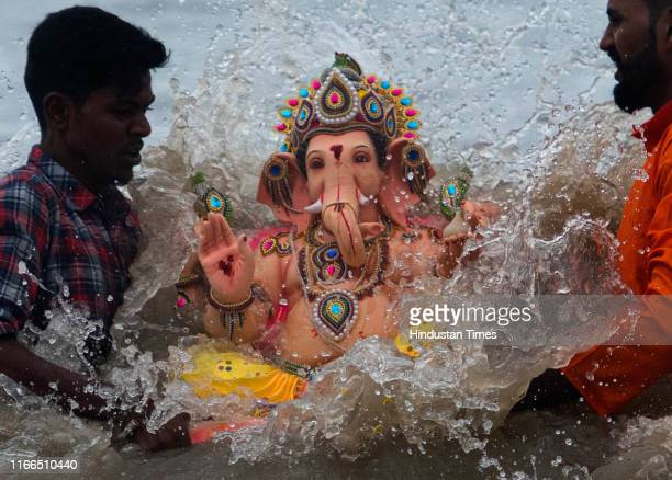 Devotees immerse a statue of Hindu God Ganesh on the fifth day of Ganesh Chaturthi Festival at Dadar Chowpatty on September 6 2019 in Mumbai India...