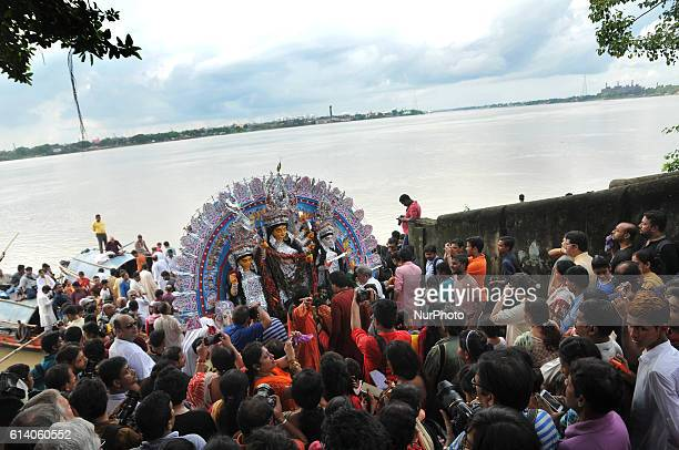 Devotees immerse a statue of the Hindu goddess Durga into the Ganges river during the immersion ceremony of Durga Puja in the eastern Indian city of...