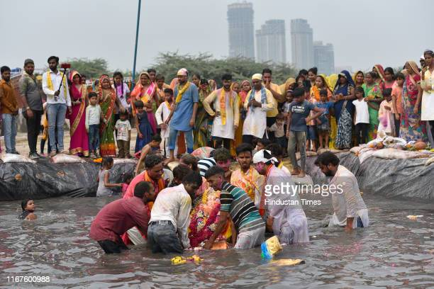 Devotees immerse an idol of Lord Ganesh at a temporary pond on the last day of the Ganesh Chaturthi festival, at Jaitpur Kalindi Kunj road on...