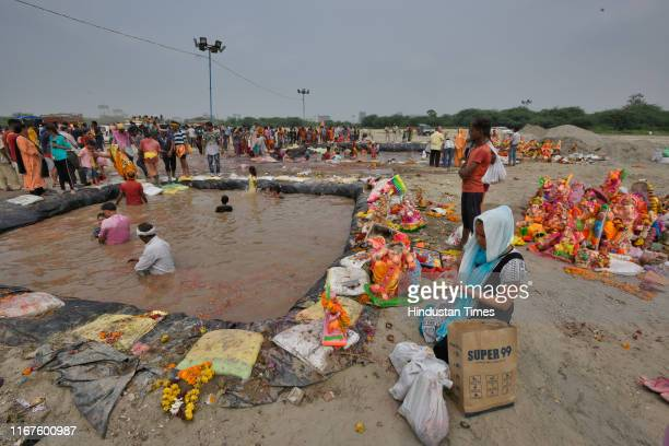 Devotees immerse idols of Lord Ganesh at a temporary pond on the last day of the Ganesh Chaturthi festival, at Jaitpur Kalindi Kunj road on September...