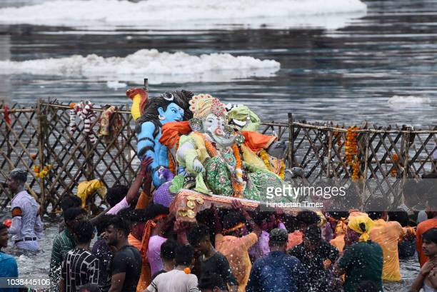 Devotees immerse a statue of Hindu God Ganesh in Juhu Beach on the last day of Ganesh Chaturthi Festival on September 23 2018 in Mumbai India The...