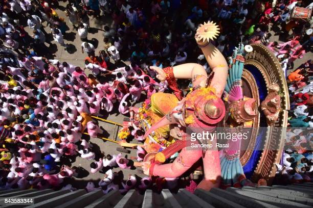 devotees in the procession with idol of the god ganesh - ganesh chaturthi stock photos and pictures