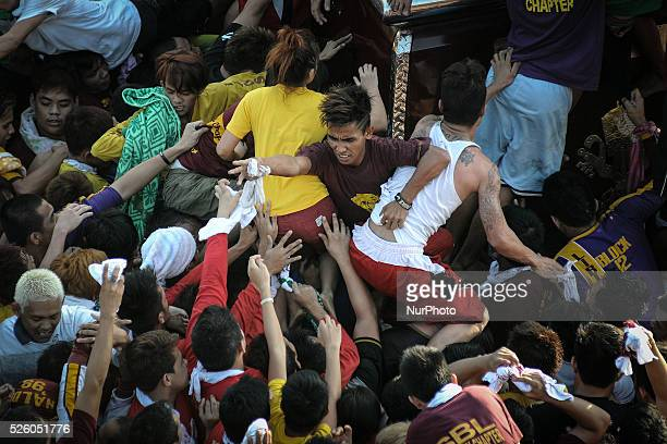 Devotees jostle one another to touch the Black Nazarene during its procession in Manila Philippines January 9 2014 The Black Nazarene is a sculpture...