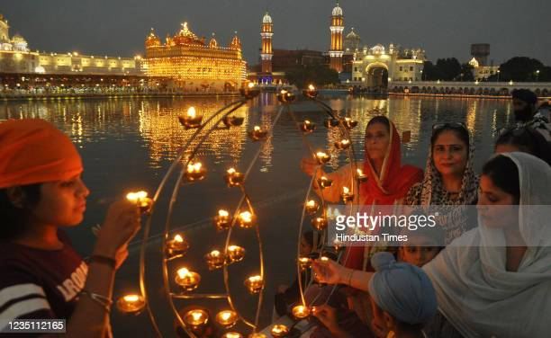 Devotees light diyas oil lamps at Golden Temple on the occasion of the 417th first installation anniversary of Sri Guru Granth Sahib on September...