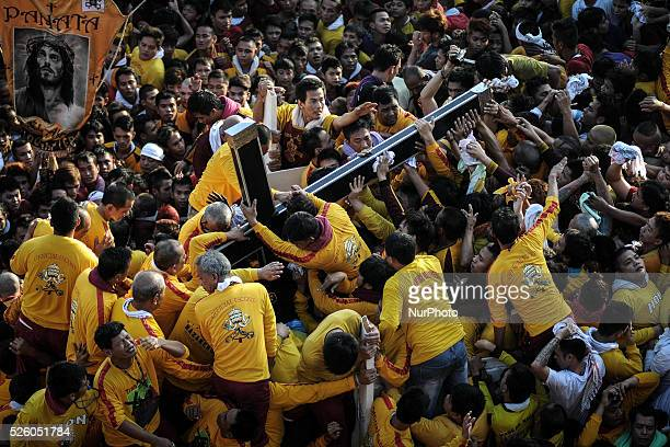 Devotees load the Black Nazarene into its carriage during its procession in Manila Philippines January 9 2014 The Black Nazarene is a sculpture of a...